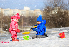 Little boy and girl digging snow in winter. Kids winter activities Royalty Free Stock Photos