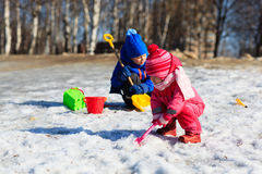 Little boy and girl digging snow in winter. Kids winter activities Stock Photography