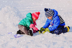 Little boy and girl digging snow in winter. Kids winter activities Stock Images