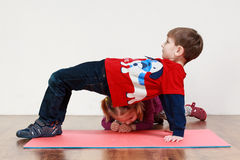 A little boy and a girl are doing an exercise at the gym royalty free stock photo