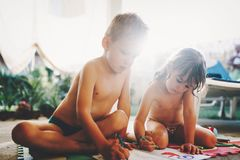 Little boy and girl drawing with crayons. On floor Stock Photo
