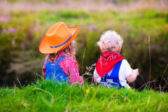 Little boy and girl dressed up as cowboy and cowgirl playing wit. H toy rocking horse in park. Kids play outdoors. Children in Halloween costumes at trick or royalty free stock image