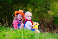 Little boy and girl dressed up as cowboy and cowgirl playing wit. H toy rocking horse in park. Kids play outdoors. Children in Halloween costumes at trick or stock images