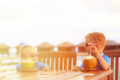 Little boy and girl drinking coconut cocktail on Royalty Free Stock Images