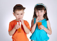 Little boy and girl drinking juice Stock Images