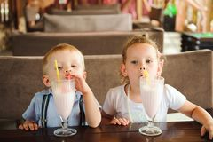 Little boy and girl drinking milkshakes in a cafe outdoors. Little boy and girl drinking milkshakes in a cafe outdoors stock images