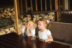 Little boy and girl drinking milkshakes in a cafe outdoors. Little boy and girl drinking milkshakes in a cafe outdoors stock photos