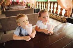 Little boy and girl drinking milkshakes in a cafe outdoors. Little boy and girl drinking milkshakes in a cafe outdoors royalty free stock image