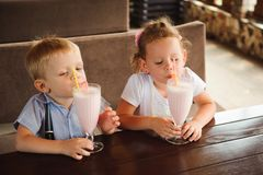 Little boy and girl drinking milkshakes in a cafe outdoors. stock photography