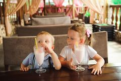 Little boy and girl drinking milkshakes in a cafe outdoors. Little boy and girl drinking milkshakes in a cafe outdoors royalty free stock photos