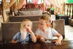 Little boy and girl drinking milkshakes in a cafe outdoors.  royalty free stock images