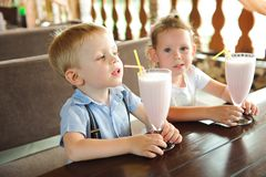 Little boy and girl drinking milkshakes in a cafe outdoors. Little boy and girl drinking milkshakes in a cafe outdoors stock image
