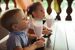 Little boy and girl drinking milkshakes in a cafe outdoors. Little boy and girl drinking milkshakes in a cafe outdoors royalty free stock photo