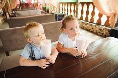 Little boy and girl drinking milkshakes in a cafe outdoors. Little boy and girl drinking milkshakes in a cafe outdoors stock photography