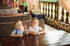 Little boy and girl drinking milkshakes in a cafe outdoors.  stock photos