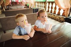 Little boy and girl drinking milkshakes in a cafe outdoors. Little boy and girl drinking milkshakes in a cafe outdoors royalty free stock images