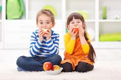 Little boy and girl eating apples stock photos