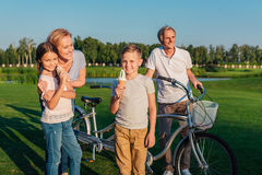 Children eating ice cream. Little boy and girl eating ice cream with grandparents with bicycle near by Stock Photos