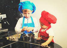 Little boy and girl enjoy cooking in kitchen Royalty Free Stock Images