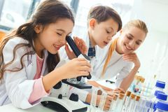 Little kids with teacher in school laboratory looking in microscope royalty free stock photos