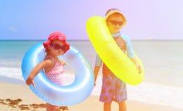 Little boy and girl go swim on beach Stock Photos