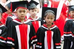 Little boy and girl graduated from kindergarten school Stock Image