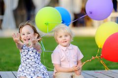Little boy and girl having fun and celebrate birthday party with colorful balloons royalty free stock image