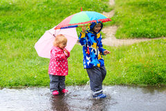 Little boy and girl having fun on rain. Kids play outdoors stock photos