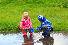 Little boy and girl having fun on rain. Kids play outdoors stock image