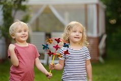 Little boy and girl having fun during walk. Happy child with pinwheel royalty free stock photography