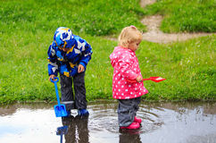 Little boy and girl having fun with water at rain. Little boy and girl having fun on rain, kids play outdoors royalty free stock photography