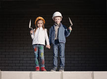 Little boy and girl in helmets build house Stock Images