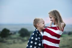 Little boy and girl holding American flag 4th of July independence day stock photo