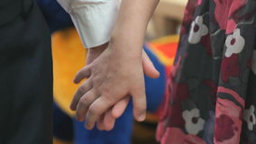 Little boy and girl holding hands in kindergarten. Little boy and girl standing each other holding hands at the  kindergarten stock video footage