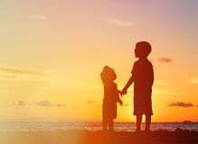 Little boy and girl holding hands at sunset Stock Photo