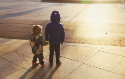 Little boy and girl holding hands in sunset city Royalty Free Stock Photo
