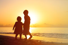 Little boy and girl holding hands walking at sunset Royalty Free Stock Image