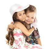 Little boy and girl hugging isolated over white. Portrait of funny little boy and a cute girl hugging Stock Images