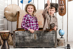 Little boy and girl with jewelry sitting in chest. Smiling little boy and girl with jewelry sitting in big old chest Royalty Free Stock Image