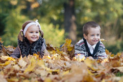Little boy and girl laying down on grass Stock Images