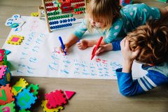 Little boy and girl learn to write and calculate numbers stock images