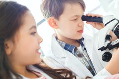 Little kids learning chemistry in school laboratory looking in a microscope close-up. Little boy and girl learning in school laboratory boy looking in a Royalty Free Stock Photography