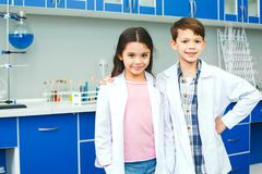 Little kids learning chemistry in school laboratory best friends. Little boy and girl learning in school laboratory standing together hugging best friends future royalty free stock image