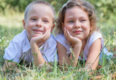 Little boy and the girl lie together on a grass Stock Images
