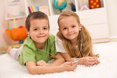 Little boy and girl listening to music together. Sharing earphones, laying on the floor at home Stock Photos