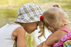 Little boy and girl look at each other Stock Image