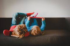 Little boy and girl looking at touch pad at home. Comfort and technology royalty free stock photography