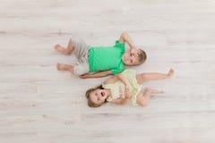 Little boy and girl lying on the floor. stock photography