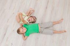 Little boy and girl lying on the floor. Stock Photo