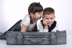 Little boy and girl lying on suitcase Stock Photos